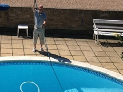 Swimming pool maintenance engineer cleaning a pool